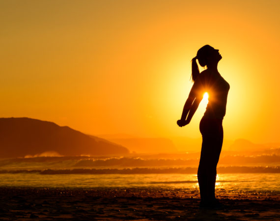 Fit woman doing yoga relaxing and breathing exercises on beach at summer sunset. Freedom, relax and harmony in nature. Female stretching arms alone.